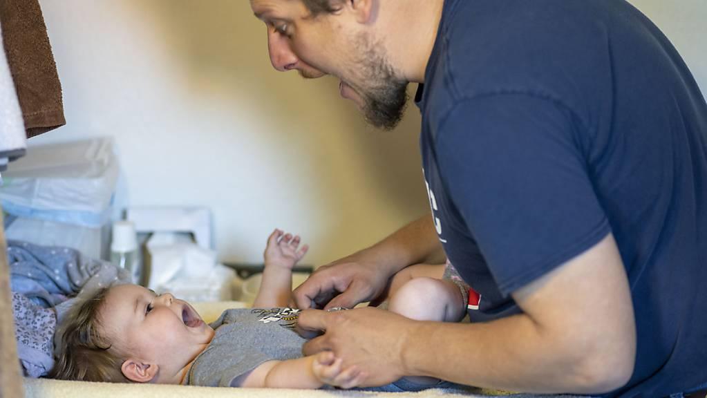 Ein Vater wickelt an seinem freien Tag zu Hause seine sechs Monate alte Tochter. (Archivbild)