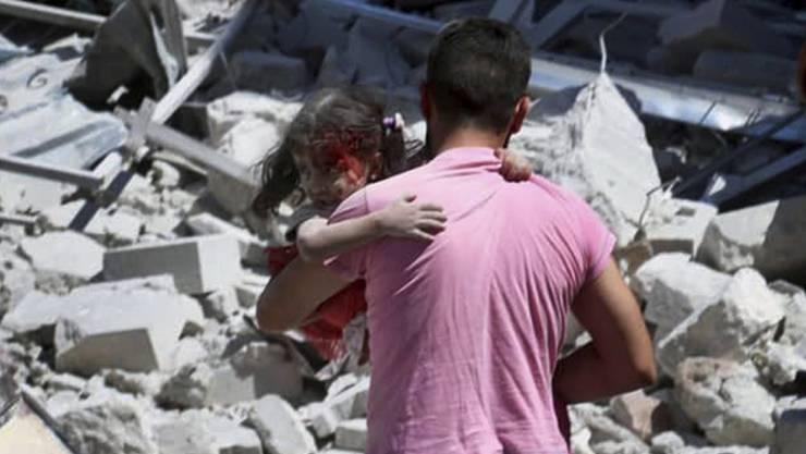 Ein Mann in Ariha, einem Ort in der syrischen Provinz Idlib, trägt ein Mädchen, das durch Luftangriffe verletzt wurde.