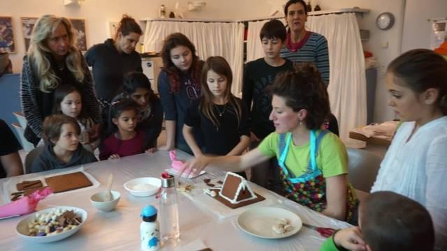 Kursleiterin Mia Peterhans zeigt den Kindern wie man ein Lebkuchenhaus baut