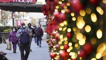 Menschen mit Mund-Nasen-Schutz gehen an Geschäften mit weihnachtlicher Dekoration vorbei. Foto: Wang Ying/XinHua/dpa