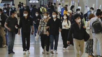 Menschen mit Mundschutz im Flughafen Gimpo in Seoul. Foto: Ahn Young-Joon/AP/dpa