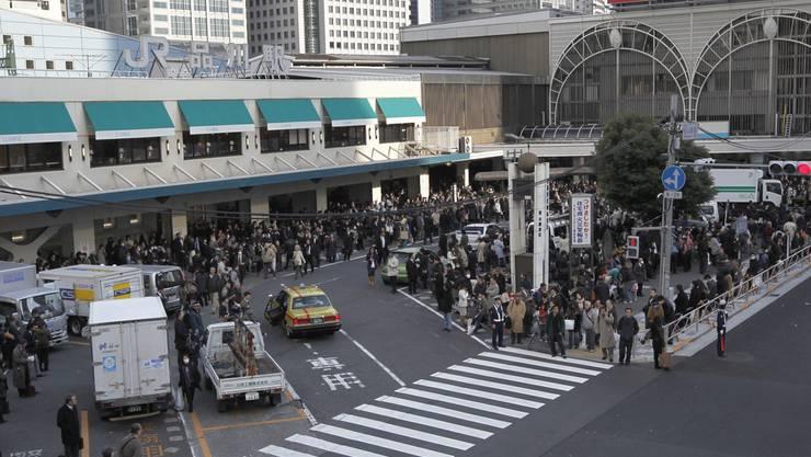 Menschen warten vor der Tokioter Bahnstation Shinagawa