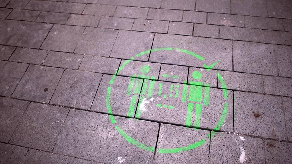 Ein Piktogramm mit dem Hinweis zum Abstandhalten ist auf das Pflaster gemalt. Foto: Federico Gambarini/dpa