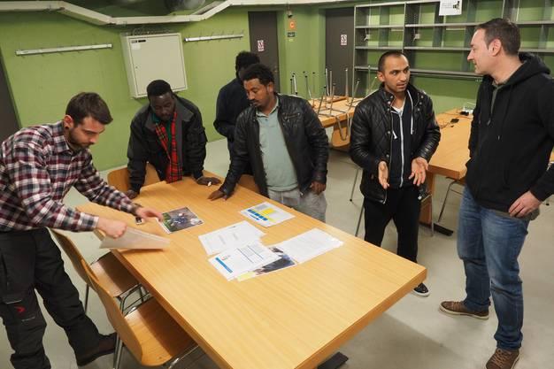 Zentrumsleiter Roman Jucker und ein Mitarbeiter erklären den Asylsuchenden ein neues Beschäftigungsprogramm mit externer Arbeit.