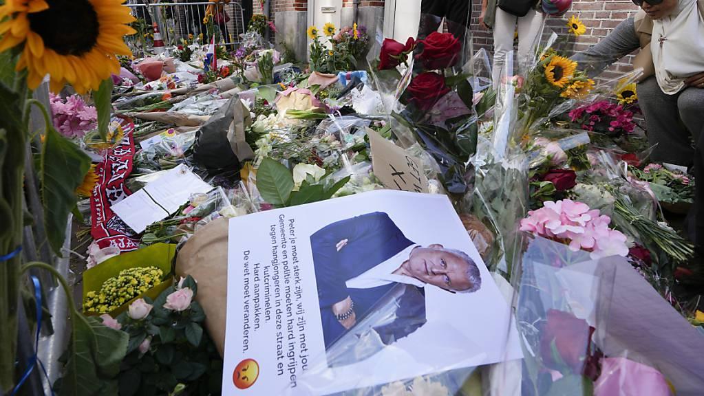 Menschen haben Bilder des Kriminalreporters Peter R. de Vries und Blumen am Tatort in Amsterdam niedergelegt. Der prominente Journalist ist nach dem Mordanschlag seinen schweren Verletzungen erlegen.