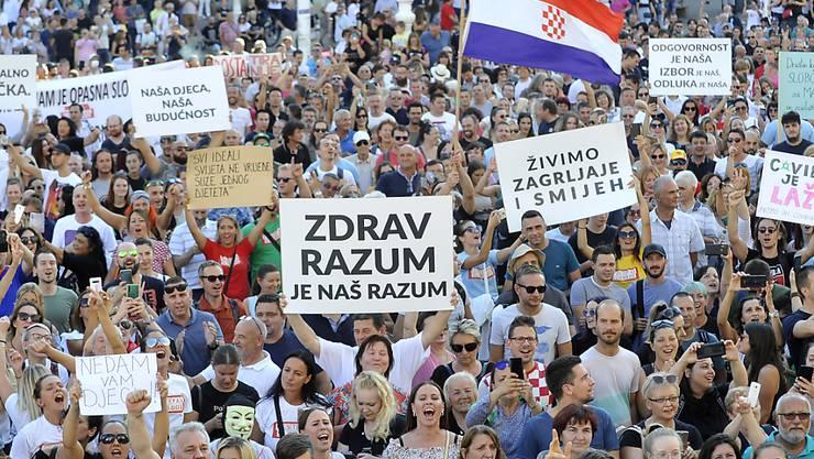 Demonstranten nehmen an einem Protest gegen Corona-Maßnahmen in Zagreb teil. Tausende Menschen haben sich zu der Demonstration in der Innenstadt versammelt. Foto: -/AP/dpa