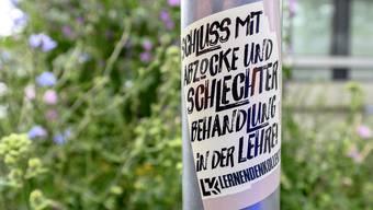 Sticker mit Forderungen hängen an Basler Strassenlaternen.