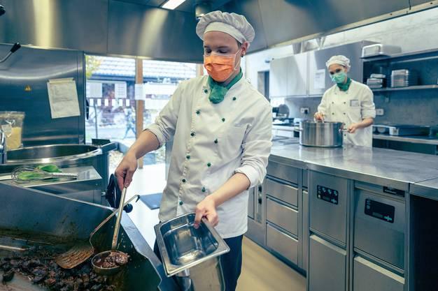 Zwei Mitarbeiter in der Betriebsküche der Stiftung Lebenshilfe. Sie kochen auch in der Quarantänesituation.