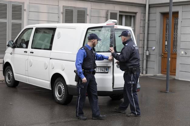 Zwei Polizisten öffnen die Tür des Wagens, in dem der Angeklagte zum Prozess gefahren wurde.