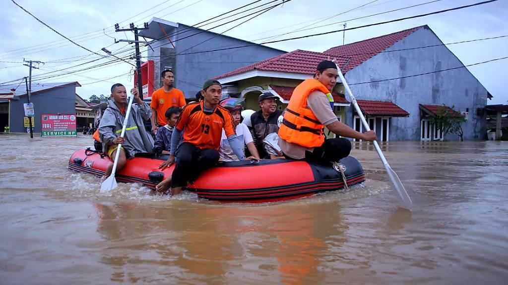 Helfer evakuieren vom Hochwasser betroffene Menschen im Süden der Insel Sulawesi.