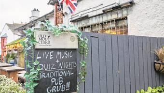 Ein klassisches Pub im nordenglischen Bowness-on-Windermere wirbt für sein altbewährtes Programm. Martin Berry/Alamy