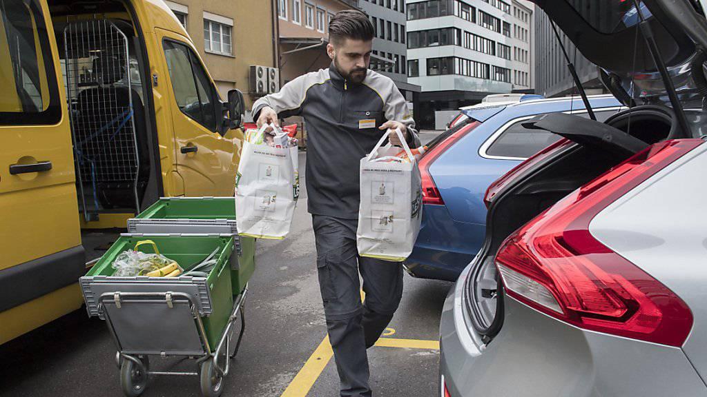 Der moderne Pöstler bei einem seiner künftigen Jobs, der Kofferraum-Zustellung. Wie seine Pensionskassen-Rente eines Tages aussehen könnte, darüber wird gerade verhandelt. (Symbolbild)