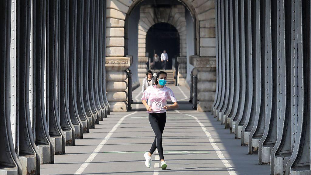 Eine Frau, die eine Schutzmaske trägt, während sie am zwölften Tag einer coronabedingten Abriegelung in Paris joggt. Seit Freitagmorgen (28. August) müssen die Menschen überall in Paris aufgrund er Corona-Pandemie unter freiem Himmel eine Maske tragen. Foto: Ludovic Marin/AFP/dpa