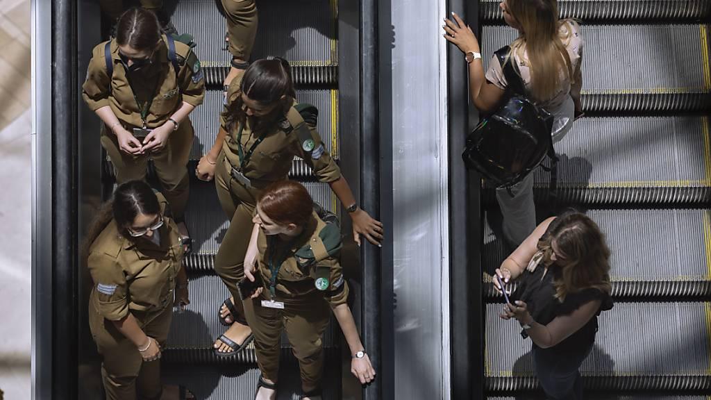 Menschen fahren ohne Mund-Nasen-Bedeckung und nahe nebeneinander auf einer Rolltreppe in einem Einkaufszentrum in Tel Aviv. Foto: Oded Balilty/AP/dpa