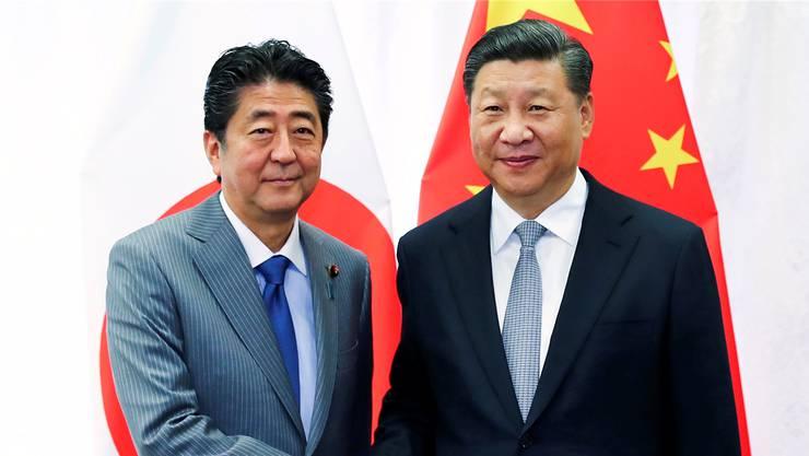 Sollen sich (wie hier im September an einem Asien-Gipfel) bald wieder die Hände schütteln: Japans Premier Shinzo Abe und Chinas Präsident Xi Jinping.