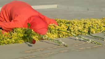Eine Frau trauert am Grab von Rafik Hariri in Beirut. 15 Jahre nach der Ermordung des damaligen libanesischen Premierministers hat ein Sondertribunal das Urteil gegen vier Angeklagte verkündet: Einer wurde verurteilt, die drei anderen freigesprochen. Foto: Marwan Naamani/dpa