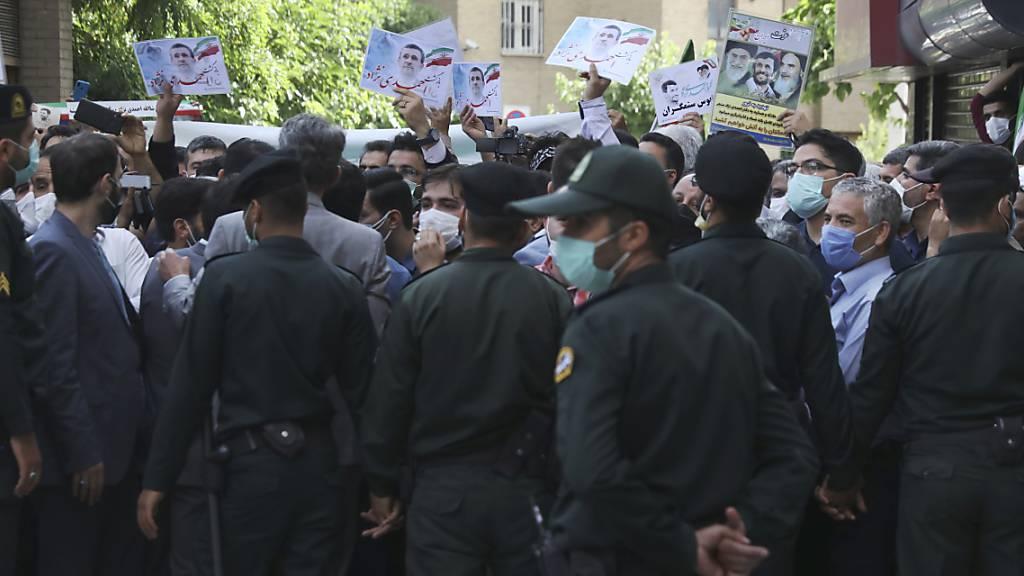 Unterstützer des ehemaligen Präsidenten Ahmadinejad halten Plakate mit seinem Konterfei, während er sich im Innenministerium als Kandidat für die Präsidentschaftswahlen am 18. Juni registriert. Polizisten hindern die Unterstützer daran sich dem Gebäude des Ministeriums zu nähern. Foto: Vahid Salemi/AP/dpa