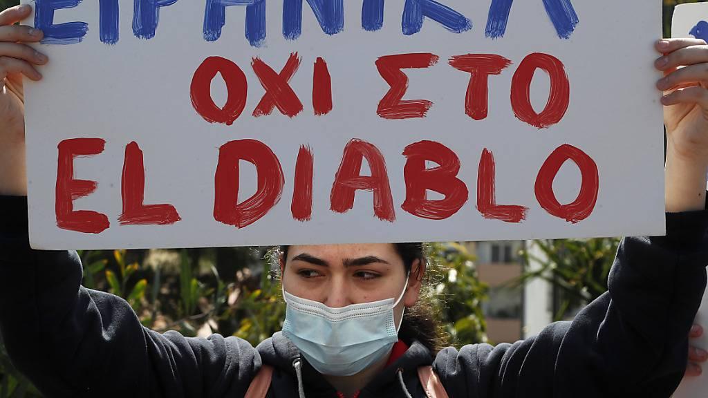 Eine Demonstrantin hält ein Schild mit der Aufschrift «Friedlich gegen El Diablo» vor dem nationalen Rundfunkgebäude Zyperns in die Höhe. Foto: Petros Karadjias/AP/dpa