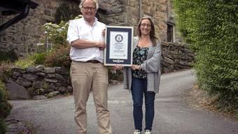 Zwei Anwohner stehen mit dem Rekord-Zertifikat auf der steilsten Strasse der Welt: Die Ffordd Pen Llech hat eine Steigung von 37,45 Prozent.
