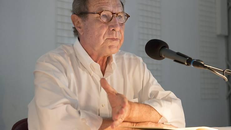 """Michael Krüger, bis Ende 2013 Verleger beim Hanser-Verlag und Autor, hat Probleme mit seinen Büchern und mit seinen drei Goethe-Ausgaben im Besonderen: Die Bücherstapel sind so hoch, dass ihm """"der Goethe auf den Kopf"""" zu fallen droht. (Archivbild)"""