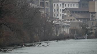 In kurzer Entfernung zum Ufer ist im Wasser die Spundwand, markiert mit rot-weiss angemalten Stangen erkennbar.