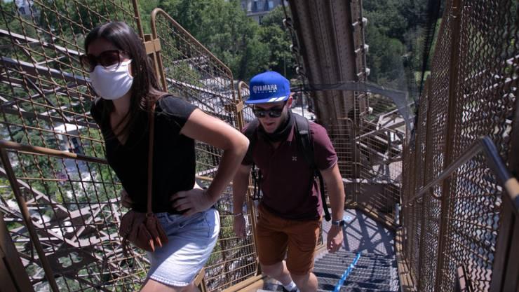Touristen steigen eine Treppe des Eiffelturms empor. Nach einer über dreimonatigen Zwangspause wegen der Corona-Krise hat der Pariser Eiffelturm am Donnerstag seine Pforten wieder geöffnet. Besucher können zunächst nur über die Treppen den zweiten Stock des Turms erreichen, die Aufzüge sollen erst vom 1. Juli an wieder öffnen. Foto: Andreina Flores/SOPA Images via ZUMA Wire/dpa