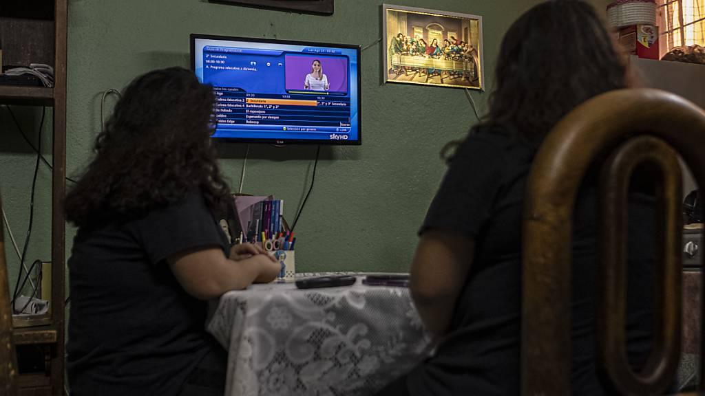 ARCHIV - Die 13-jährigen Zwillinge Ana Vanesa und Maria Fernanda verfolgen den Unterricht im Fernseher, als das neue Schuljahr wegen der Corona-Pandemie mit Unterricht per Fernsehen und Radio begonnen hat. Foto: Jacky Muniello/dpa