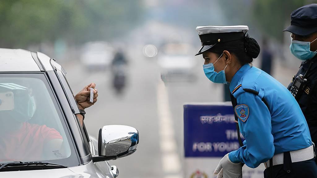 Polizisten kontrollieren die Fahrzeugpapiere am vierten Tag des landesweiten Lockdowns. Angesichts rasch steigender Corona-Fallzahlen streicht Nepal Flugverbindungen für rund zwei Wochen. Foto: Prabin Ranabhat/SOPA Images via ZUMA Wire/dpa