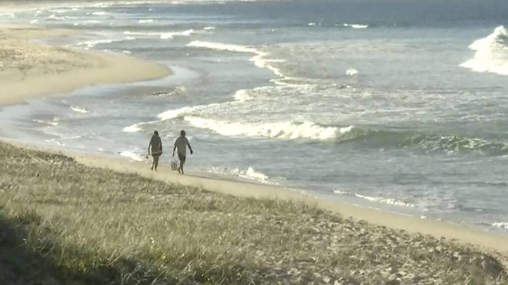 In diesem Standbild aus einem Video gehen Menschen an einem Strand in Tuncurry, Australien entlang. Foto: Uncredited/Australian Broadcasting Corporation via AP/dpa