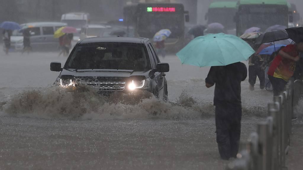 Ein Auto fährt in der zentralchinesischen Provinz Henan über eine überflutete Straße. Foto: Yuanxiaoqiang/CHINATOPIX/AP/dpa