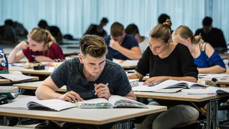 Lehrlinge schreiben konzentriert ihre Prüfungen.