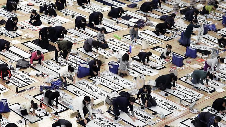 Bei einem Kaligraphie-Wettbewerb in Tokio bemühen sich rund 3000 Japaner um die kunstvollsten Schriftzeichen.