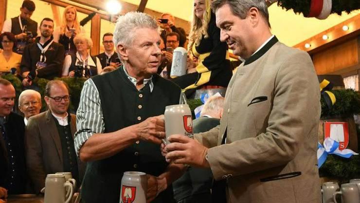 Der Münchner Oberbürgermeister Dieter Reiter überreicht dem bayerischen Ministerpräsidenten Markus Söder nach dem traditionellen Fassanstich einen Masskrug.