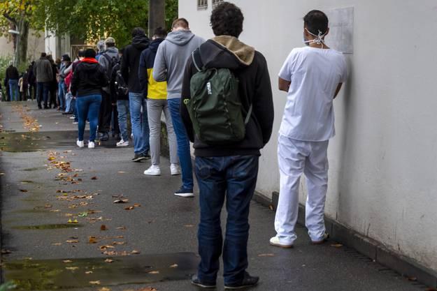 Menschen stehen Schlange vor dem Covid-19 Testzentrum des Universitätsspitals in Basel.