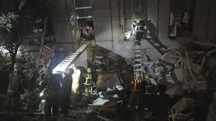 Rettungskräfte in der taiwanesischen Stadt Tainan bergen nach dem Erdbeben Verschüttete aus einem Wohngebäude.