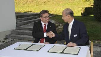 Die Hand drauf: Takakazu Ishii, der Gouverneur von Toyama, und der Baselbieter Regierungspräsident Urs Wüthrich unterzeichnen bei Bad Schauenburg die Vereinbarung. (Bild: Martin Töngi)