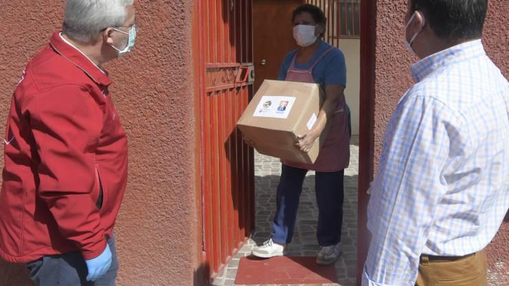 Eine Frau in Iquique bekommt ein Lebensmittelpaket. Angesichts der Corona-Krise hat die Regierung in Chile Zehntausende Lebensmittelpakete an Bedürftige verteilt. Foto: Cristian Vivero Boornes/Agencia Uno/dpa