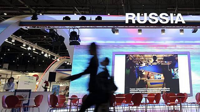Besucher laufen vor dem russischen Stand vorbei