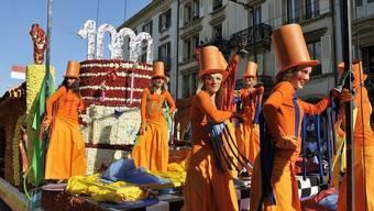 Ganz in Orange präsentieren diese jungen Frauen den Geburtstagskuchen für die 1000-jährige Stadt