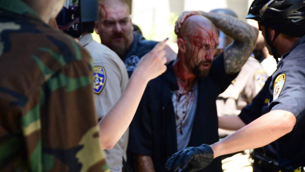 Polizisten begleiten einen Verwundeten nach den Auseinandersetzungen in Sacramento.