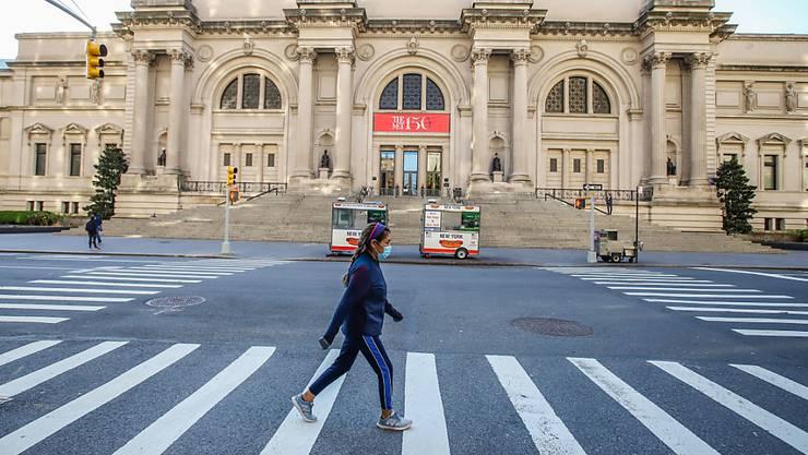 ARCHIV - Eine Frau mit Mundschutz geht vor dem Metropolitan Museum of Art in New York über die Straße. Foto: Vanessa Carvalho/ZUMA Wire/dpa