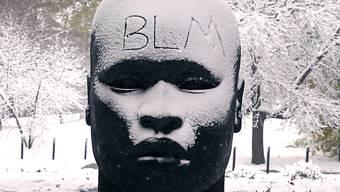 """ARCHIV - """"BLM"""" steht auf der verschneiten Stirn der Skulptur «Eternal Presence» vor dem «National Center of Afro-American Artists» geschrieben. Die Abkürzung «BLM» steht für die Menschenrechtsbewegung """"Black Lives Matter"""". Foto: Charles Krupa/AP/dpa"""