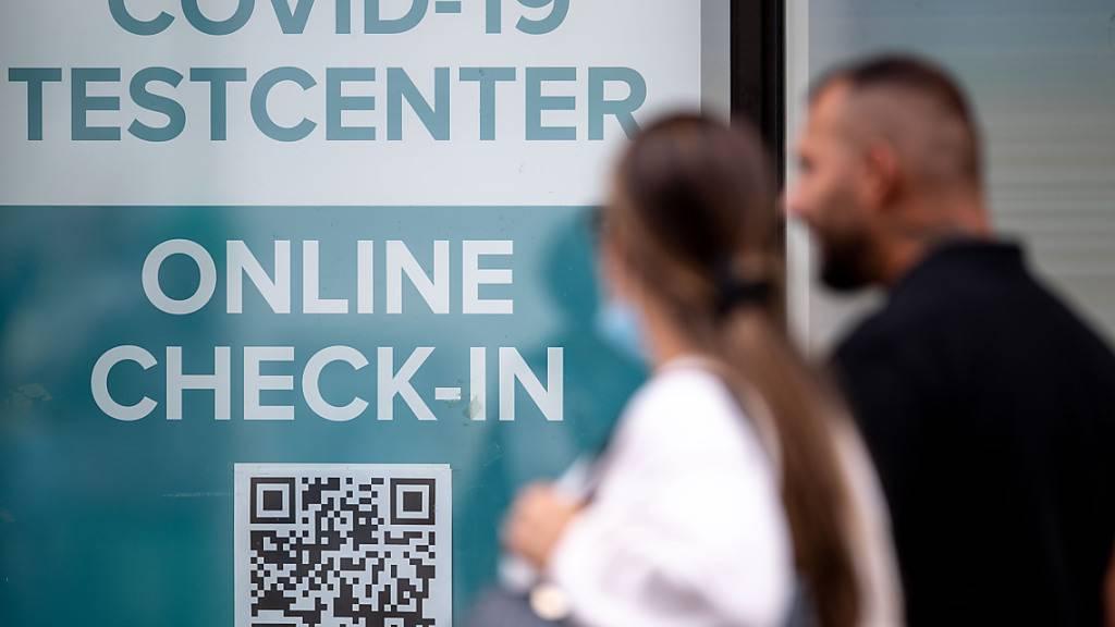 Zwei Menschen gehen an einem Kölner Covid-19 Testcenter vorbei. In Deutschland liegt erstmals seit drei Monaten die Sieben-Tage-Inzidenz der Corona-Neuinfektionen wieder über 50. Nach Angaben des landesweit in der Pandemie federführenden Robert Koch-Instituts sind vor allem junge Menschen betroffen. Foto: Marius Becker/dpa