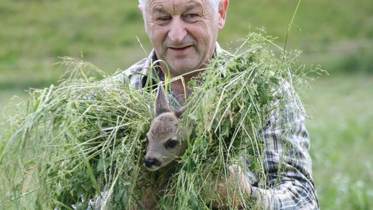 Jäger Paul Wirth rettet ein Rehkitz aus einem Feld. ZVG