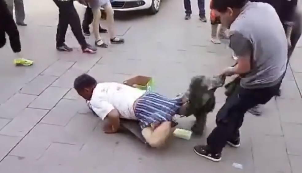 Ein Passant zieht diesem Bettler die Hosen runter – statt keinen kommen gut verpackte Beine zum Vorschein.