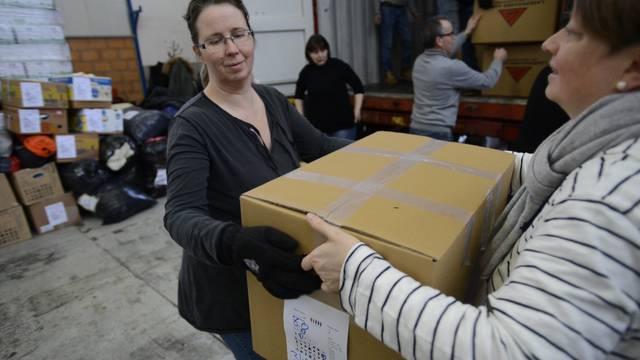 Hand in Hand: Helfer beladen die Container mit den Hilfsgütern für die Flüchtlinge.