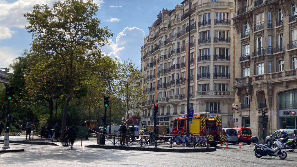 Einsatzkräfte stehen in einer nach einer Messerattacke abgesperrten Straße im 11. Stadtbezirk. Dabei  sind mindestens vier Menschen verletzt worden. Der Vorfall ereignete sich in der Nähe der ehemaligen Redaktionsräume des Satiremagazins «Charlie Hebdo». Foto: Pol O'Gradaigh/dpa