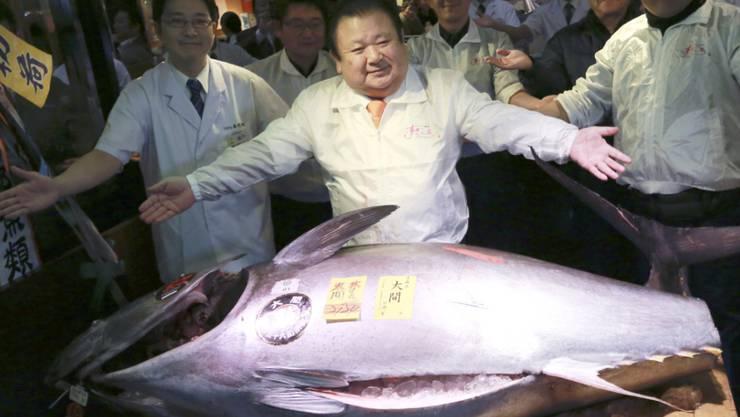 Der Gewinner der ersten Fisch-Auktion im neuen Jahr posiert stolz mit seinem Kauf.