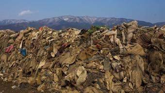Ein Kleiderberg vor einer vom Tsunami zerstörten Stadt in Japan