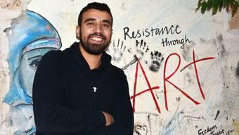 Für das Foto will sich Fajsal unbedingt neben das «Resistance through Art» (Widerstand durch Kunst)-Graffito stellen.